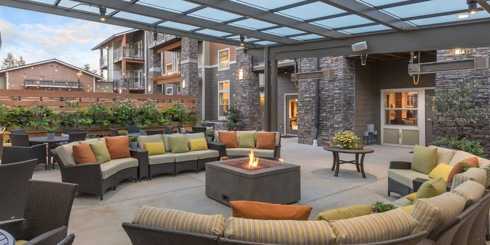 warmly lit patio with covered seating and a fire pit at The Springs at Greer Gardens in Eugene, Oregon