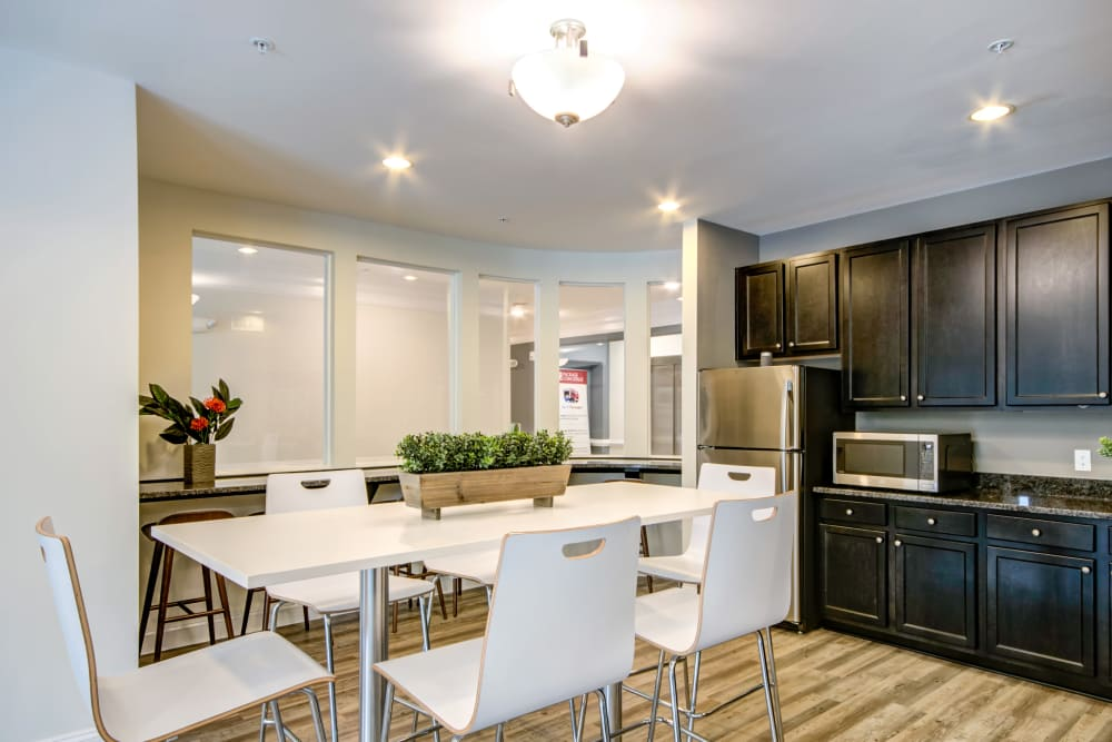 The clubhouse kitchen with tables and chairs at Manassas Station Apartments in Manassas, Virginia