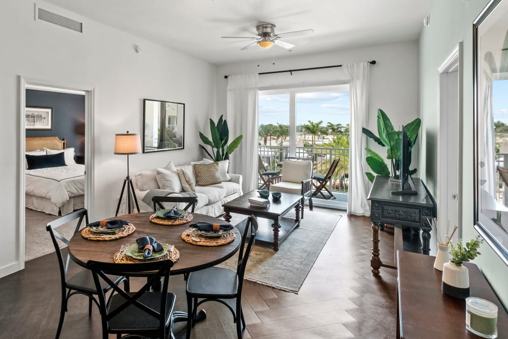 Model living room and dining area with wood style flooring at Town Lantana in Lantana, Florida