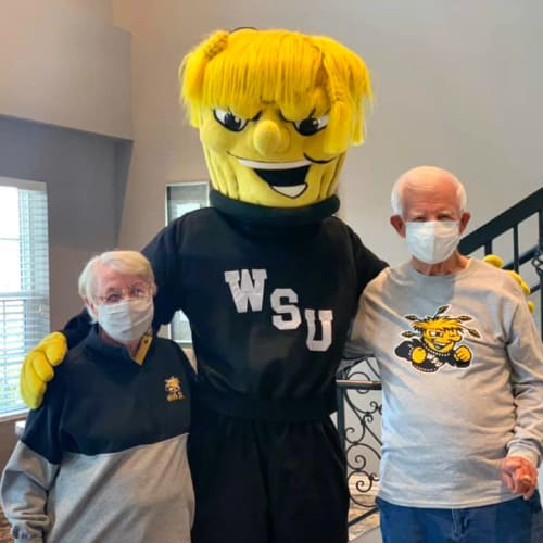 Two residents with a sports mascot at Oxford Villa Active Senior Apartments in Wichita, Kansas