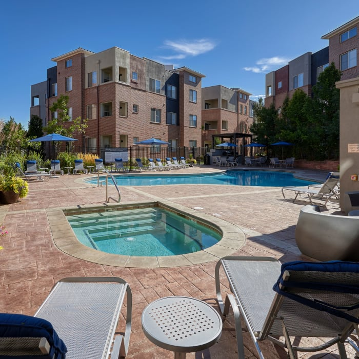 Swimming pool view with lounges and covered BBQ area and spa at The Rail at Inverness in Englewood