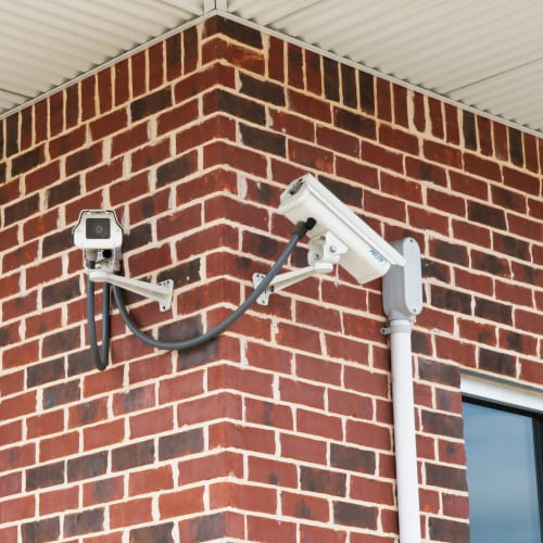 Security cameras mounted on a brick wall at Red Dot Storage in Pine Bluff, Arkansas