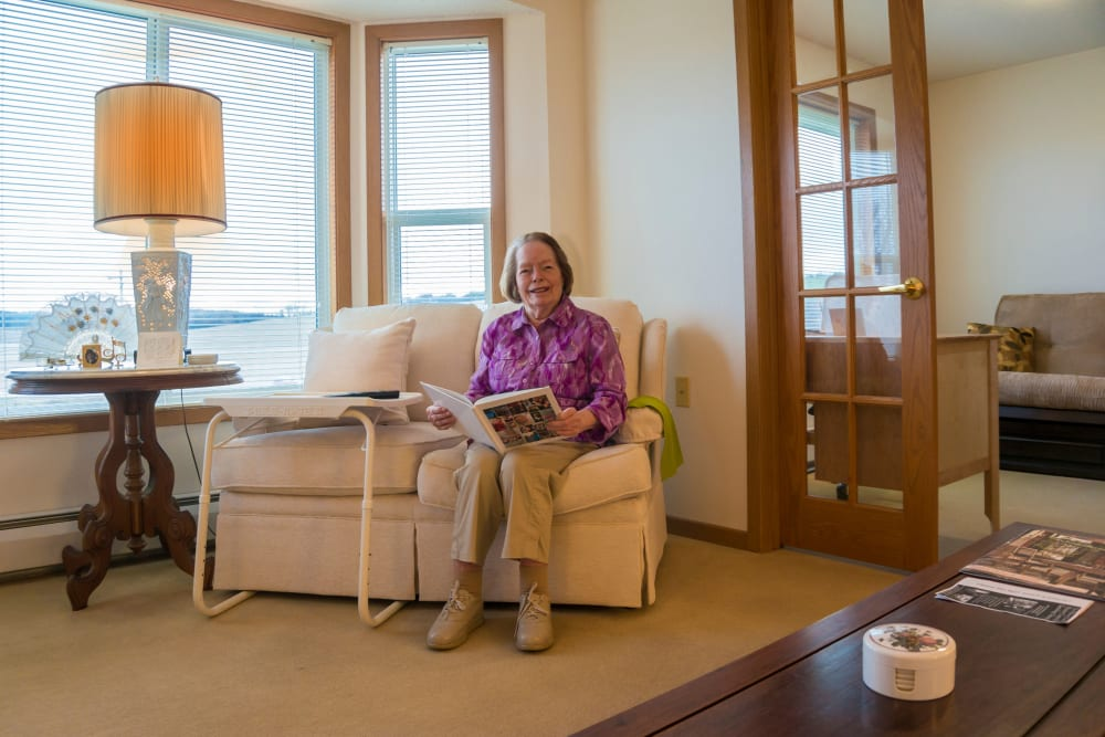 Resident enjoying comfortable living room at Meadow Lakes Senior Living in Rochester, Minnesota.