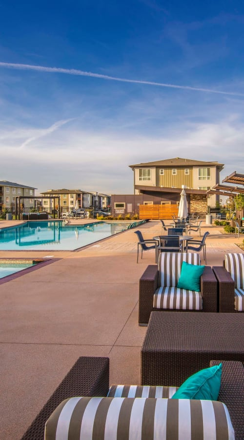 Swimming pool with cushioned lounge chairs at sunset at Strata Apartments in Denver, Colorado