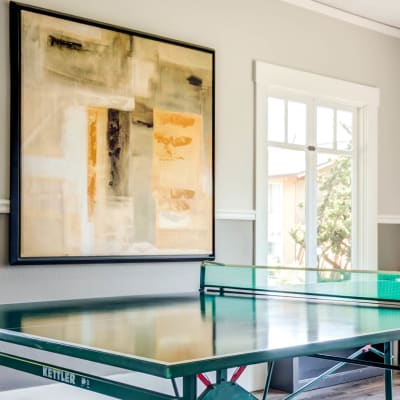 Modern art and a ping pong table in the game room at The Landmark Apartment Homes in Sunnyvale, California