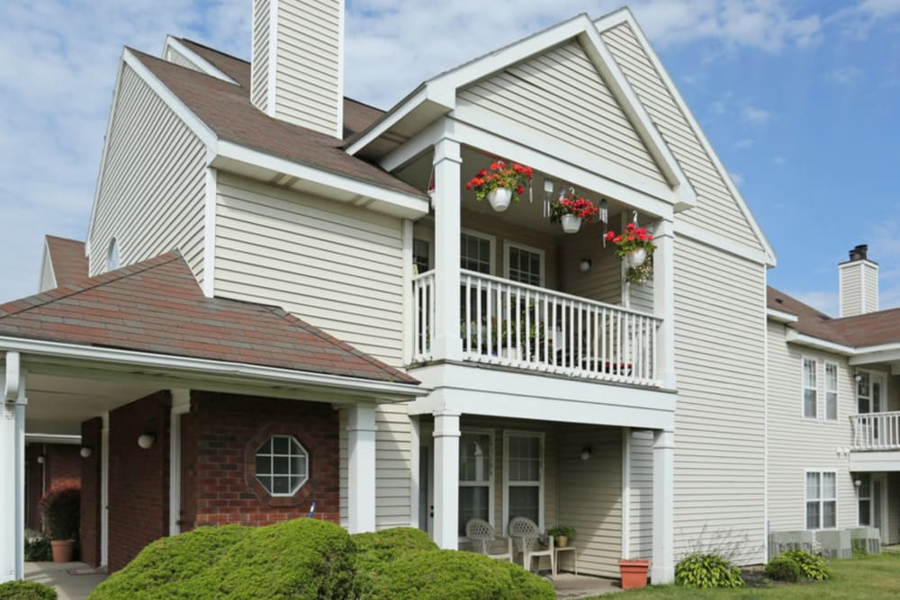 Exterior with hanging flowers at Bennington Hills Apartments in West Henrietta, New York