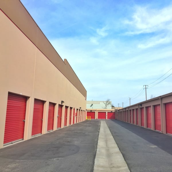 Outdoor storage units with red doors at StorQuest Self Storage in Oxnard, California