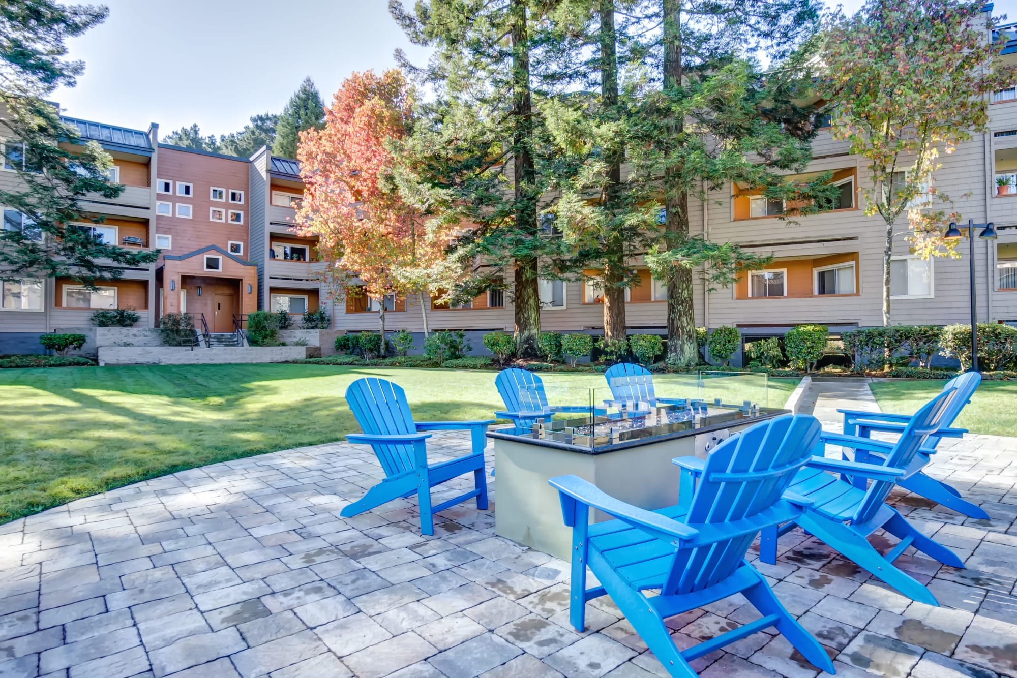 Adirondack chairs around a firepit at Serramonte Ridge Apartment Homes in Daly City, California