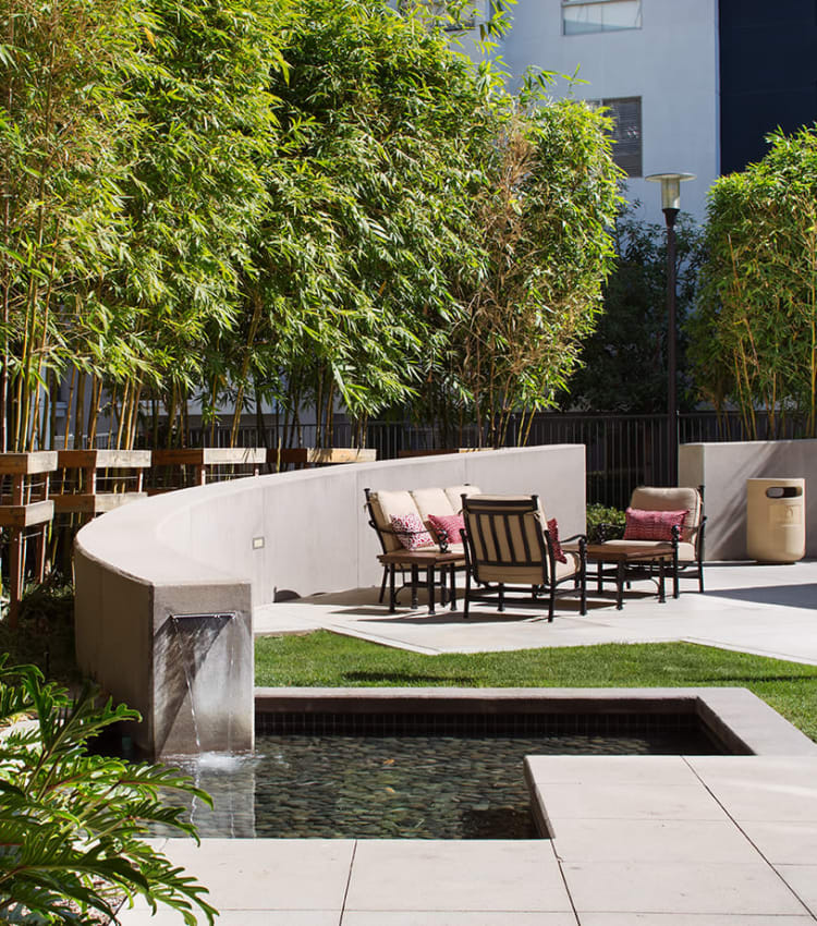 Relaxing outdoor common area with a water feature at Sofi Warner Center in Woodland Hills, California
