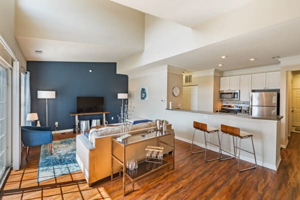 Living room and kitchen with breakfast bar at The Docks Apartments & Townhomes in Pittsburgh, Pennsylvania