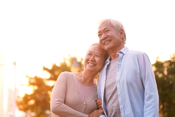 Asian senior couple hugging and smiling at something in the distance