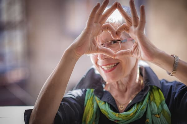 Resident making a heart sign with her hands at Pioneer Village in Jacksonville, Oregon