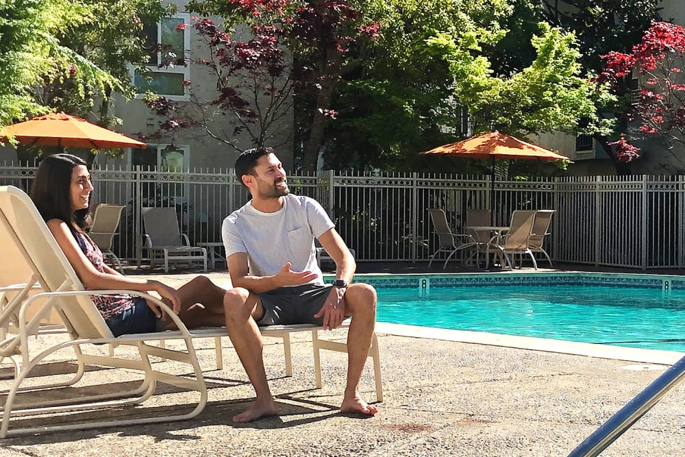 Couple relaxing the by pool at Newport Apartments in Campbell, California