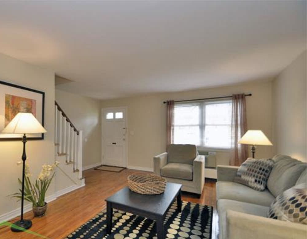 Spacious living room with cozy couch and large windows at Eagle Rock Apartments at Maplewood in Maplewood, New Jersey