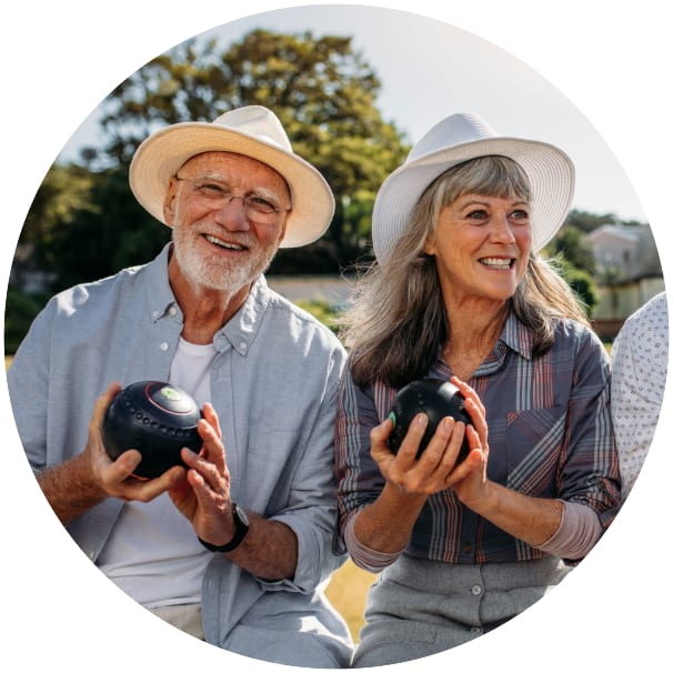 Two residents sitting outside holding weighted spheres at a Ebenezer Senior Living community