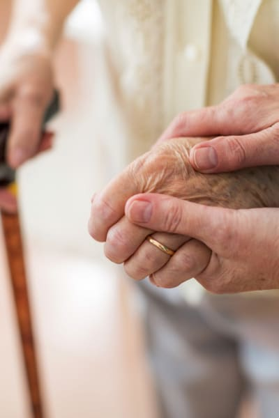 Caretaker holding the hand of a resident at a Living Care Lifestyles community