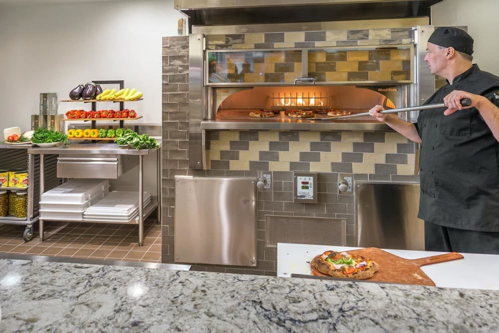 Chef artful removes flatbread from oven for enjoyment of residents at The Springs at Greer Gardens in Eugene, Oregon