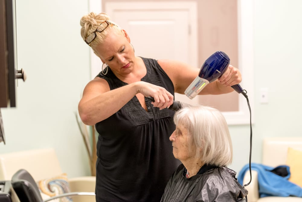 A staff member doing a resident's hair at Inspired Living at Lewisville in Lewisville, Texas