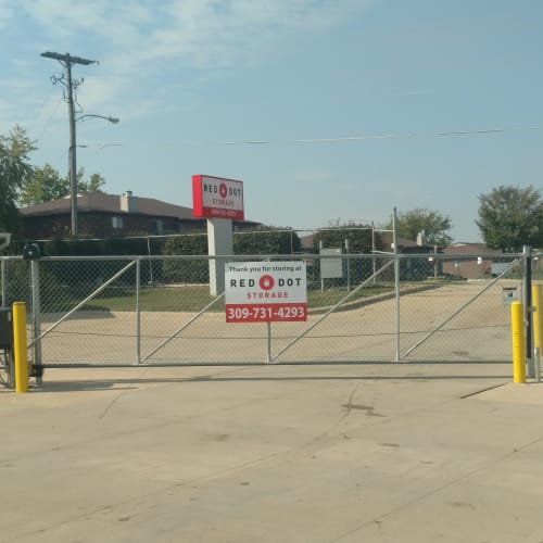 Electronic gate with a Red Dot Storage sign at the entrance to Red Dot Storage in Bloomington, Illinois