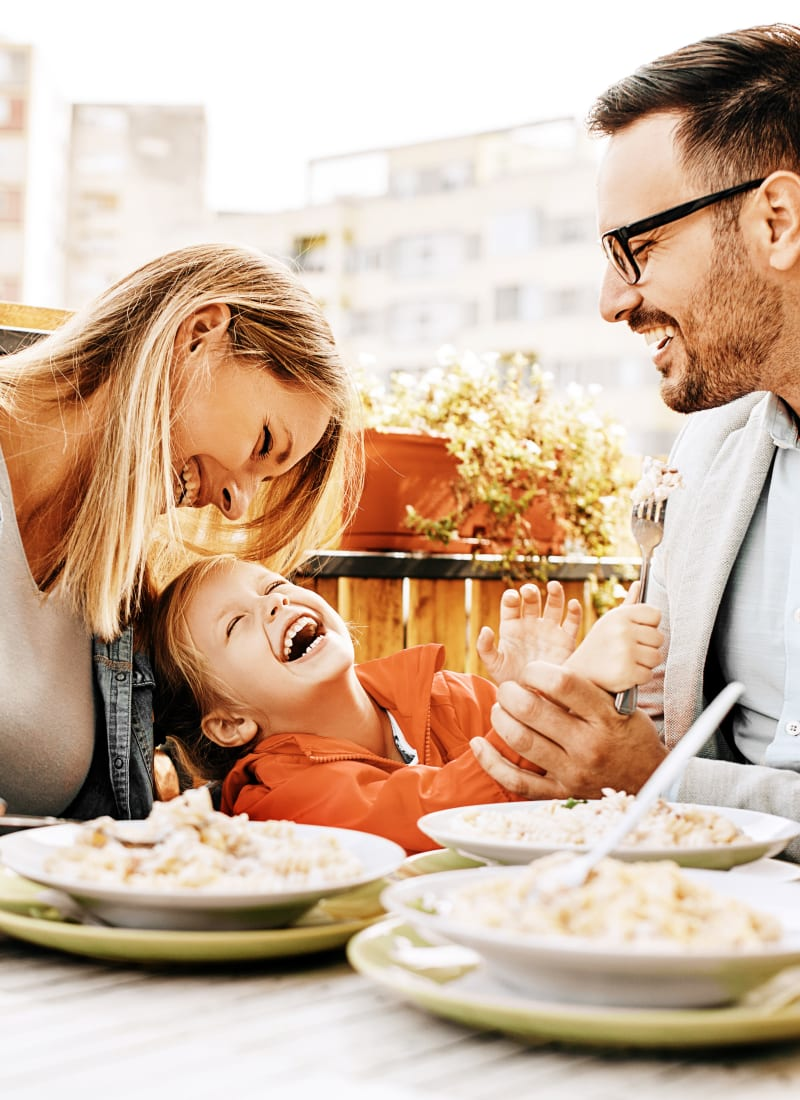 Parents and child laughing while enjoying dinner near Marquis at Katy in Katy, Texas