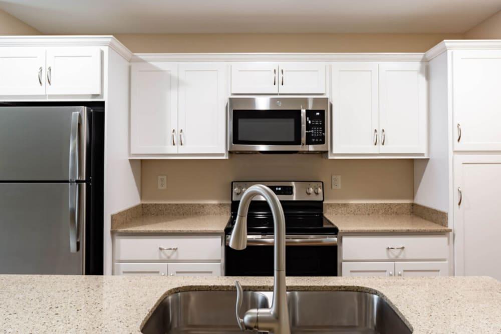Kitchen with white cabinets at Bennington Hills Apartments in West Henrietta, New York