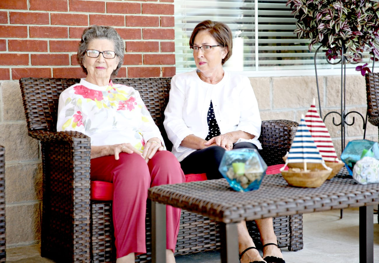 Two women sitting on an outside patio in outdoor furniture at Providence Assisted Living in Searcy, Arkansas