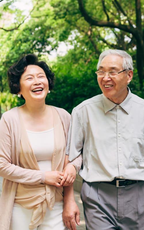 Resident couple walking through a park at Jaybird Senior Living