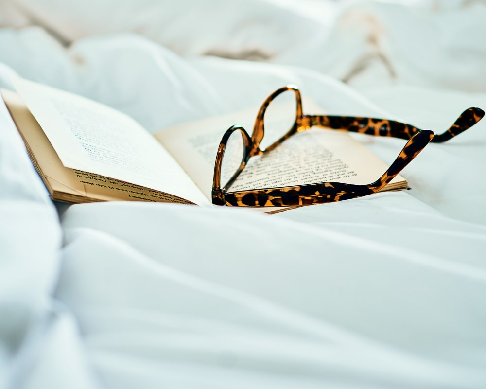 A book and reading glasses sitting on a bed at Emery Place in Robins, Iowa.