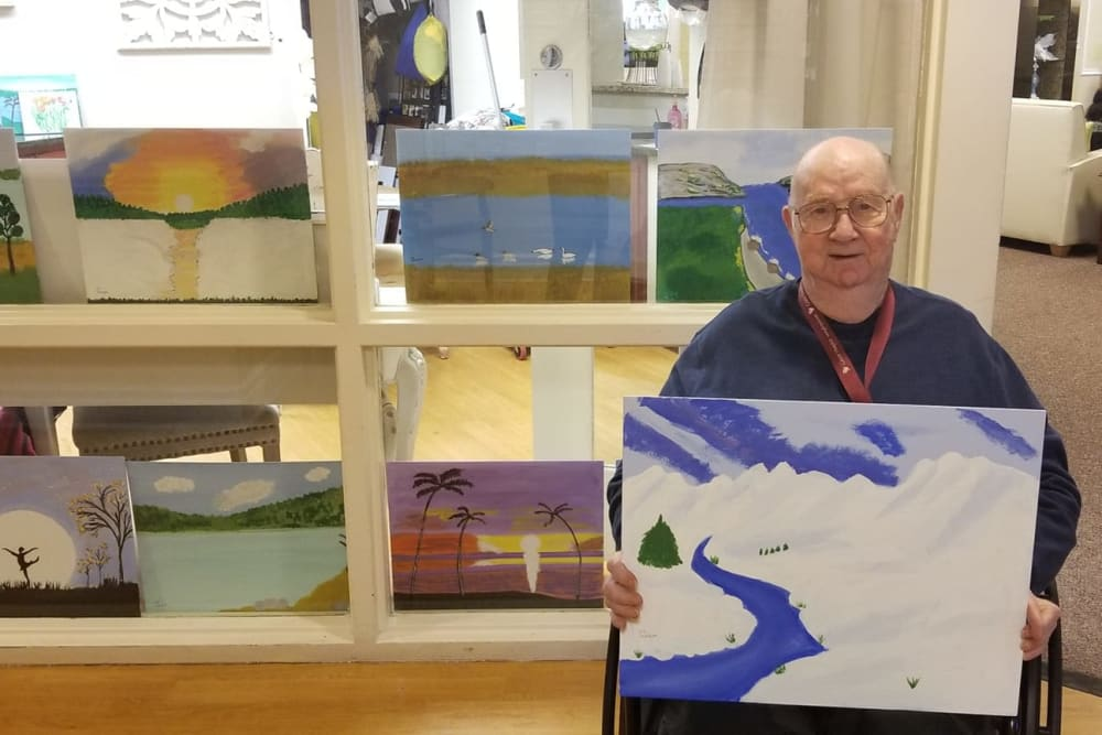 A resident holding up his painting at The Woods of Caledonia in Racine, Wisconsin