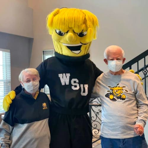 Residents posing with a sports mascot at Oxford Villa Active Senior Apartments in Wichita, Kansas
