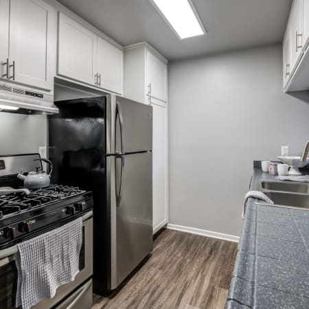 Renovated white cabinetry kitchen with stainless steel appliances at Kendallwood Apartments in Whittier