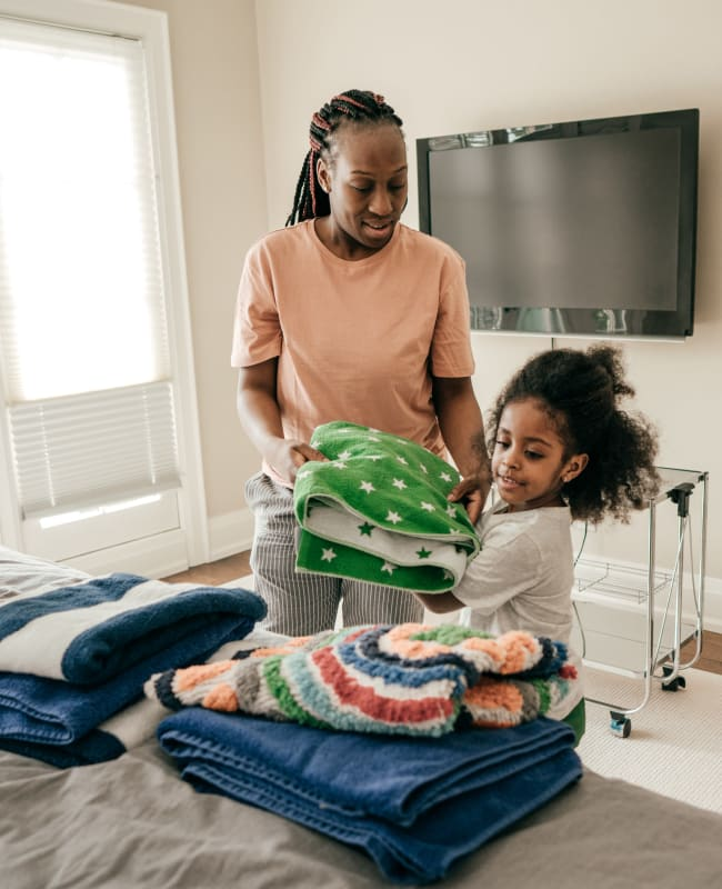 Resident and her daughter folding laundry in their spacious bedroom at Glenmont Crossing in Wheaton, Maryland