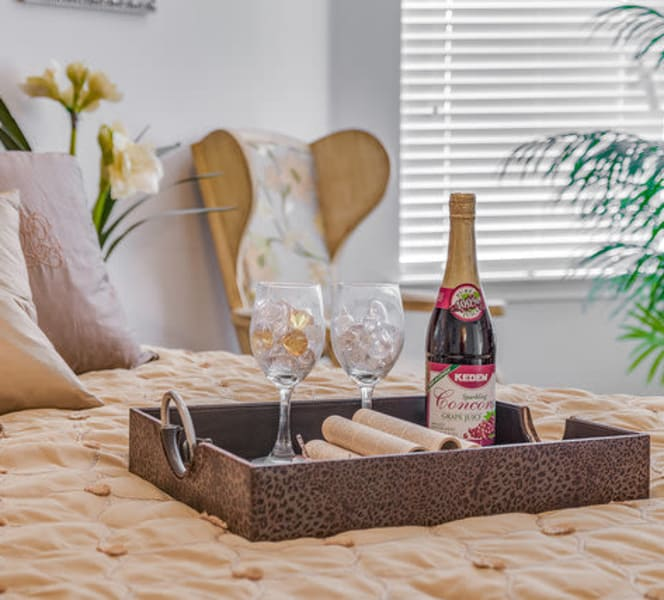 A bed with a bottle of wine and glasses at Town Village in Oklahoma City, Oklahoma