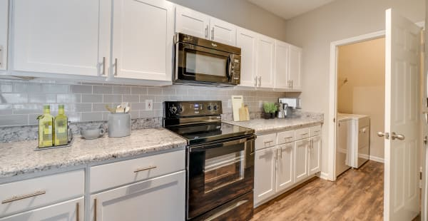 Spacious kitchen with tall chairs in model apartment home at Preston View in Morrisville, North Carolina