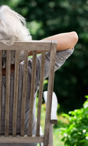 Resident sitting outside in a wooden chair at a Radiant Senior Living community