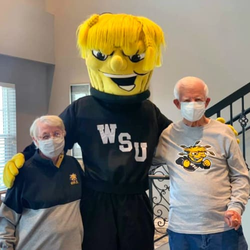 Residents standing with a sports mascot at Oxford Villa Active Senior Apartments in Wichita, Kansas