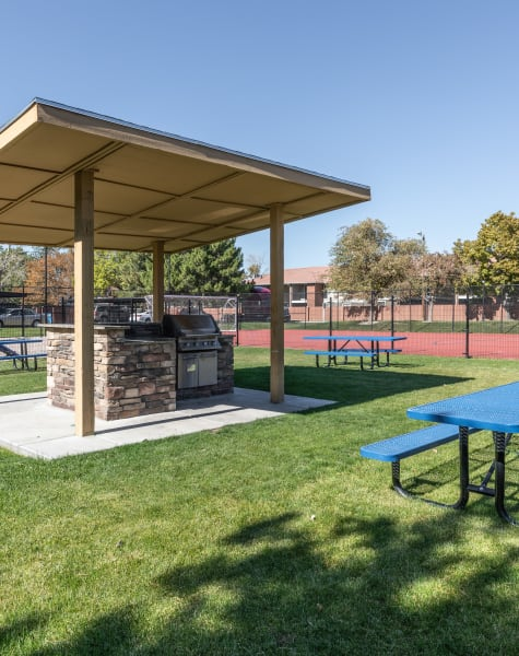 Exterior Covered BBQ Area with Picnic Table, Sport Court in the background at Shadowbrook Apartments in West Valley City