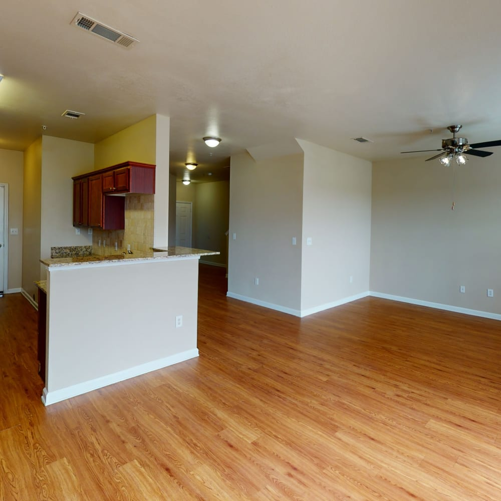 Hardwood flooring and ceiling fans in a townhome's lower-floor living areas at Oaks Estates of Coppell in Coppell, Texas