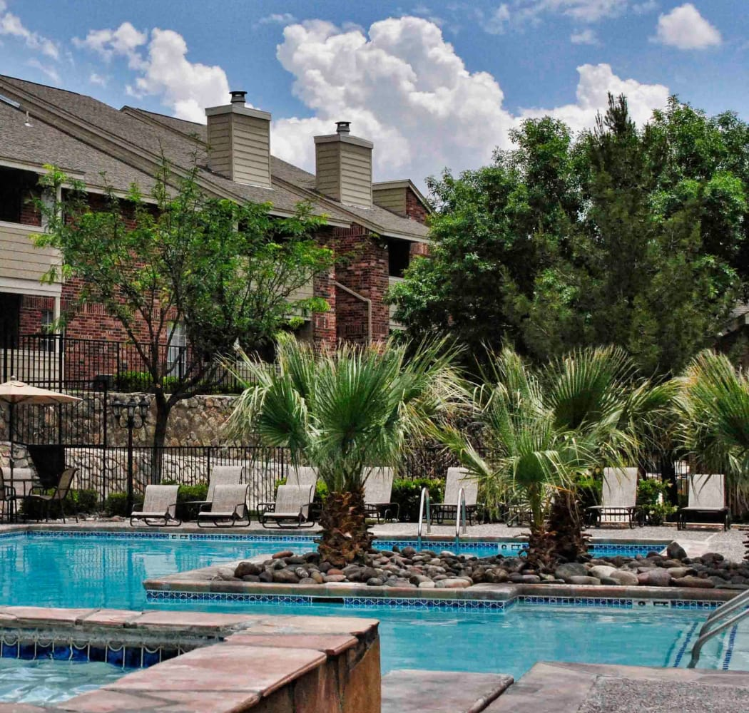 Swimming pool with small palm trees at The Chimneys Apartments in El Paso, Texas