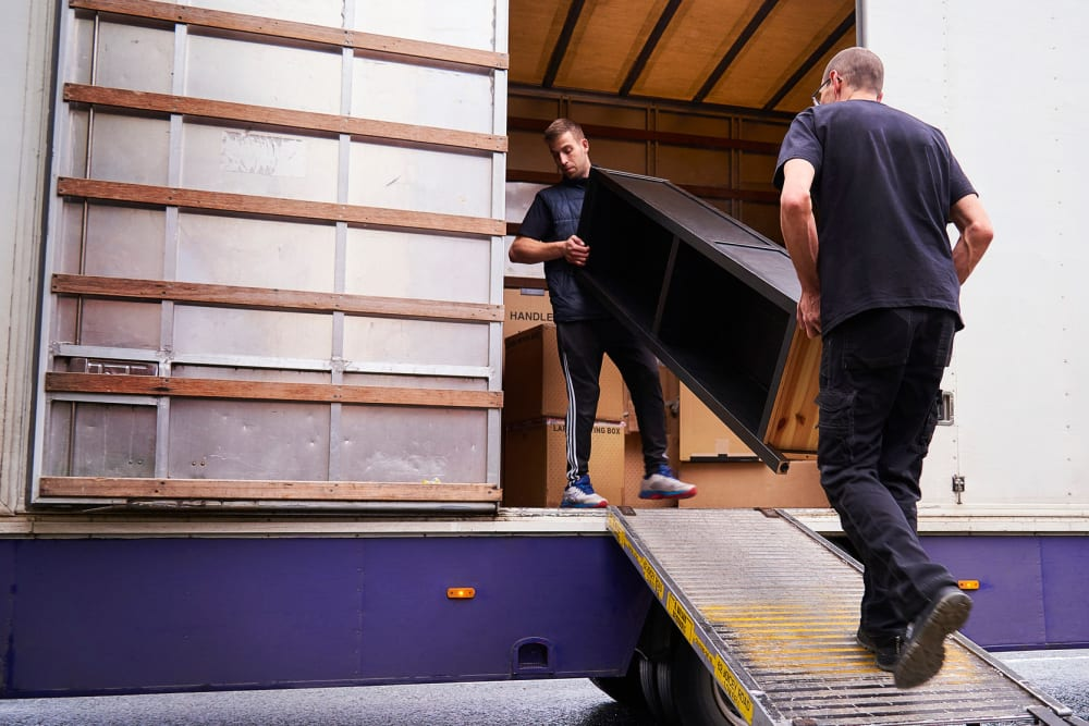 Two men loading furniture onto a moving truck at A-American Self Storage in Reno, Nevada