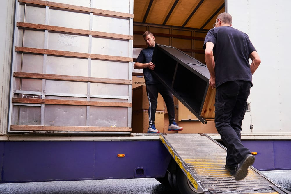 Two men loading furniture into a moving truck at A-American Self Storage in Palmdale, California