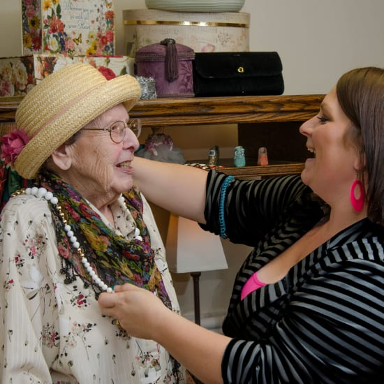 Staff helping a resident try on jewelry at Carefield Castro Valley in Castro Valley, California