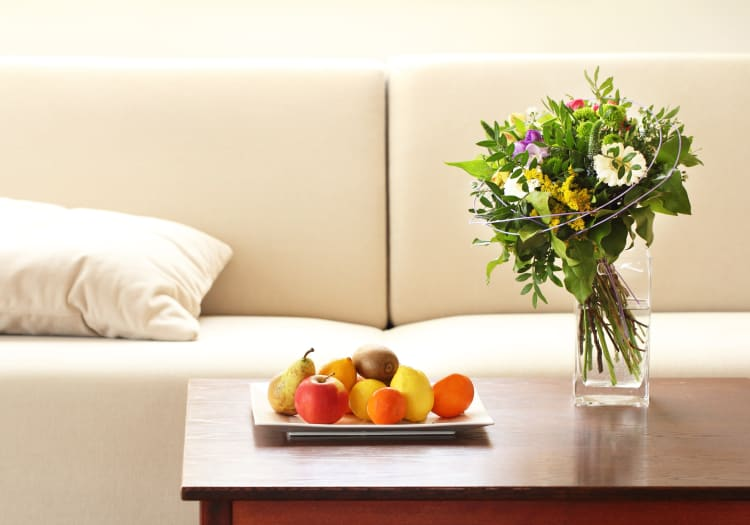 Bouquet of flowers and a plate of fruit on the coffee table in a model home at Mezza in Jacksonville, Florida