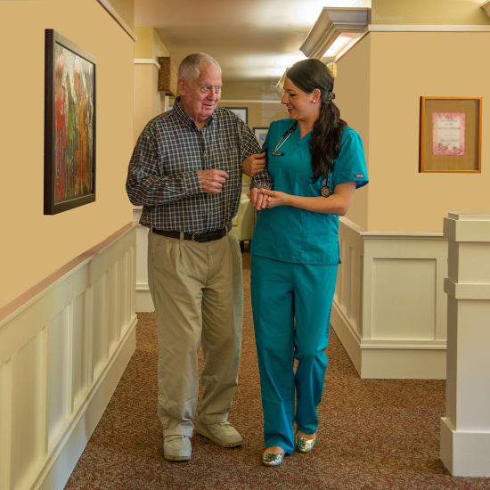 A nurse walking a resident down the hall at Madonna Gardens in Salinas, California.