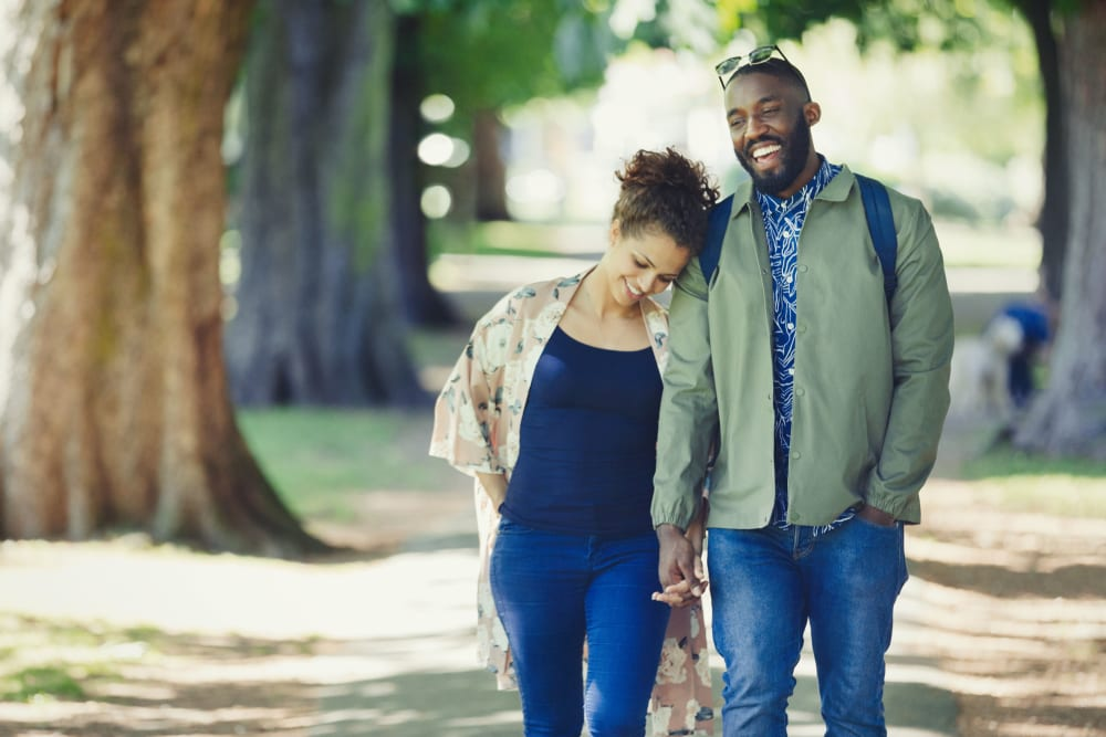Couple walking through a park in Coppell, Texas near Oaks Riverchase