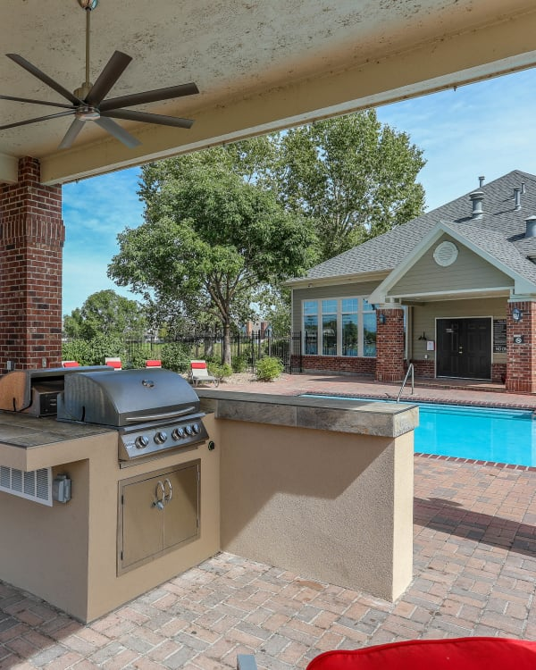 Poolside covered BBQ with bar top seating at Promenade at Hunter's Glen Apartments in Thornton