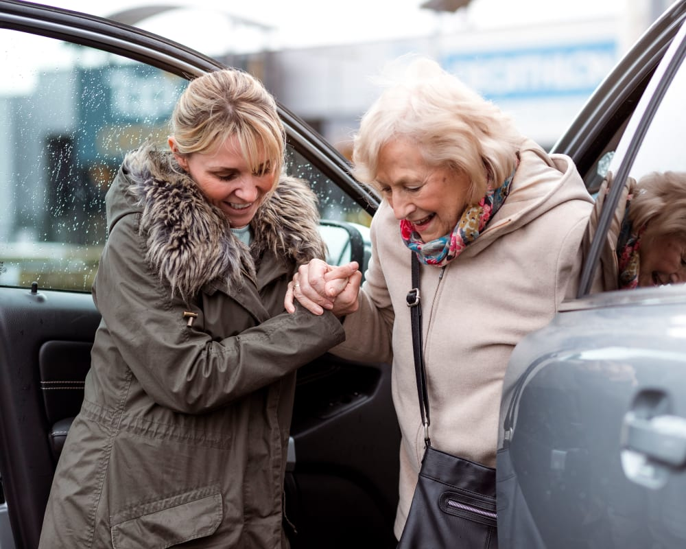 A caretaker assisting a resident out of a car at Harmony at Hershey in Hershey, Pennsylvania