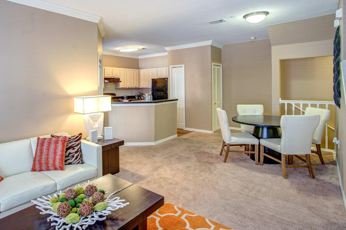 Spacious living room with plush carpeting at Amara at MetroWest in Orlando, Florida