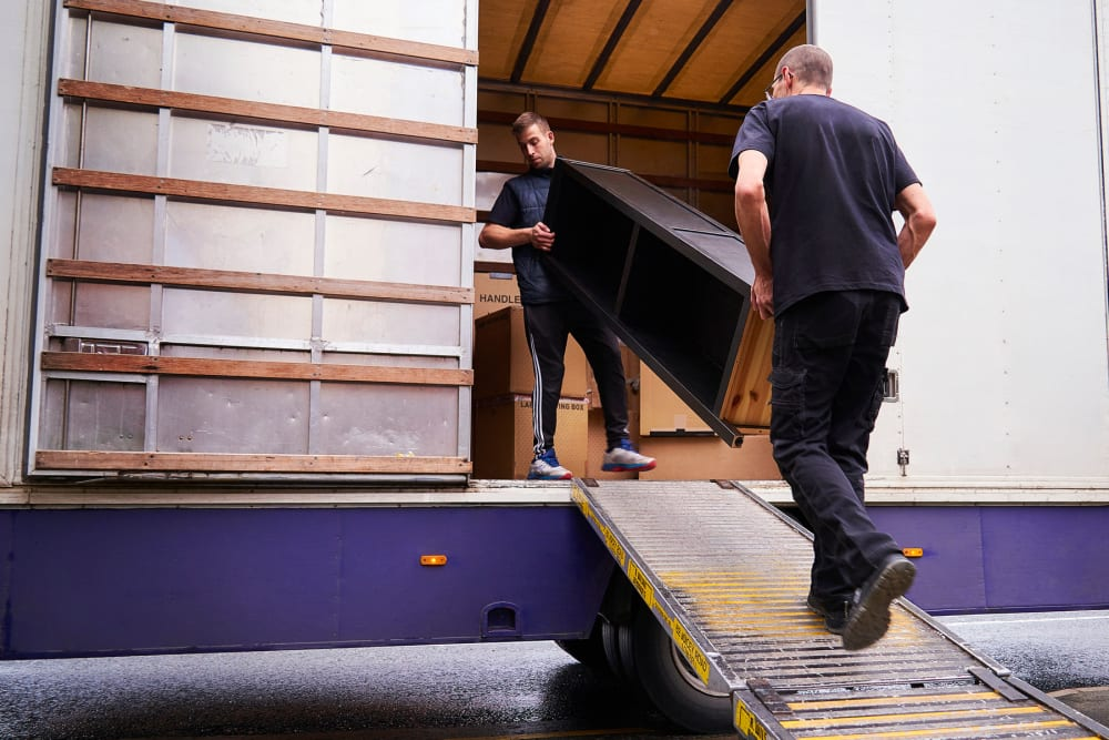 Two men loading furniture into a moving truck at A-American Self Storage in Honolulu, Hawaii