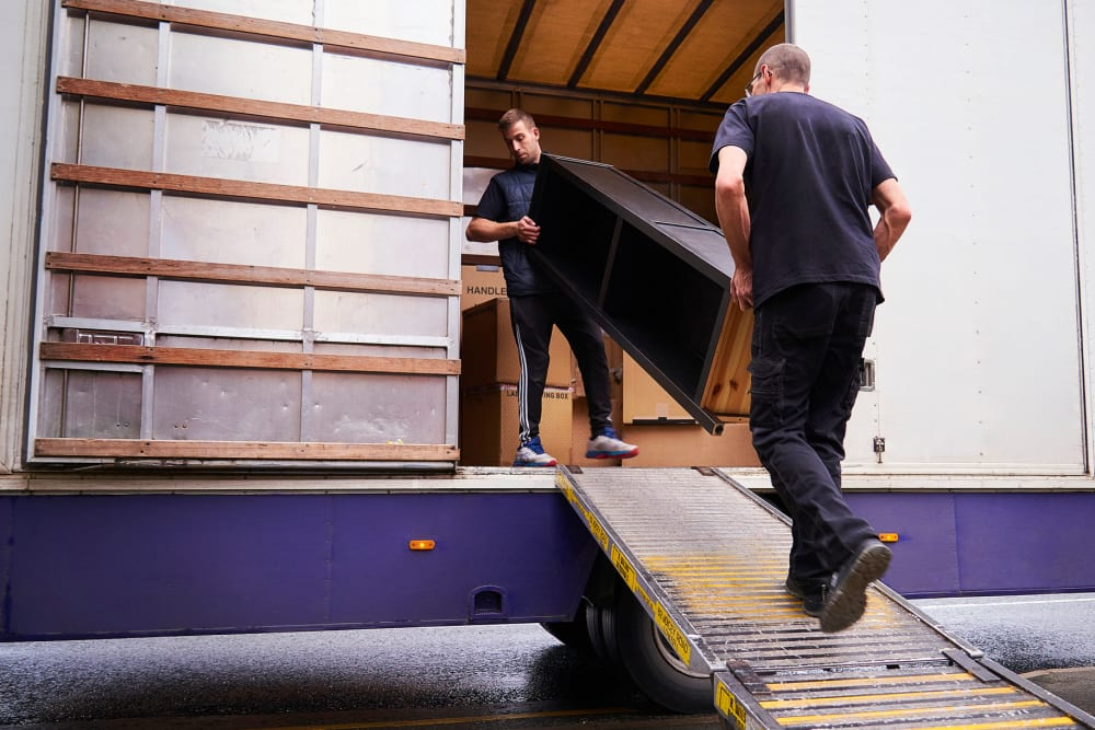 Two men loading furniture into a moving truck at A-American Self Storage in El Cajon, California